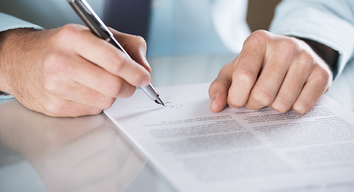 man signing insurance documents